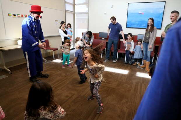 Parents and children interact with clown Frangolino during a children's story time in the Portuguese language at the Lafayette Library and Learning Center in Lafayette, Calif., on Saturday, Feb. 10, 2018. The Lafayette Library and Learning Center has several foreign language children's story time programs for the pre-school set. They read books in English, Spanish, Mandarin, French, Portuguese and Farsi. (Ray Chavez/Bay Area News Group)