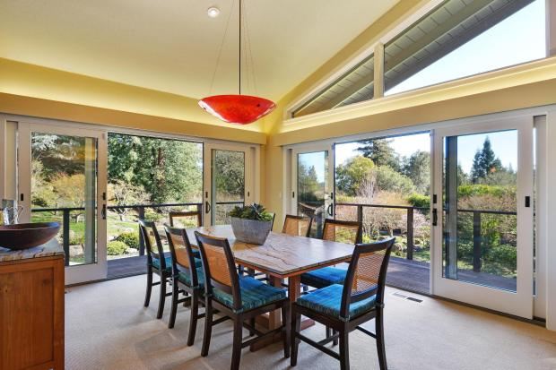 A sliding glass door in the casual dining space connects to the Ipe deck and draws in the beauty of the natural setting.