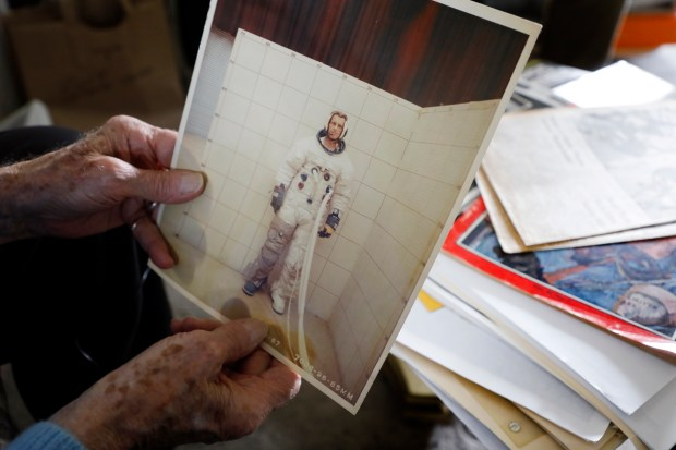 Wallace Johnson, 93, holds a photo of himself from the 1960s during ergonomic testing of a space suit as he goes through memorabilia at his home in Alameda. (Laura A. Oda/Bay Area News Group)