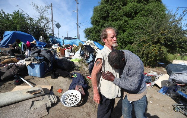 David Ball gets a hug from Ken Edward at their homeless camp near East 6th Street on Monday, April 2, 2018, in Antioch, Calif. Dozens of homeless people living on the private property have been told to prepare to leave the site by the city. (Aric Crabb/Bay Area News Group)