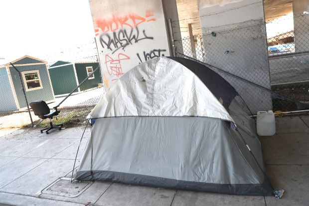 A tent is photographed along 27th Street next to a group of Tuff Shed temporary housing units on Wednesday, April 25, 2018, in Oakland, Calif. The city has leased land from Caltrans and installed 20 units that will house 40 people. (Aric Crabb/Bay Area News Group)