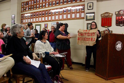 """Robin Goodman held up a sign saying """"Welcoming City"""" in Spanish."""