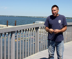 SPAT Program director Kim Tetrault, with SPAT's community oyster garden to the left.