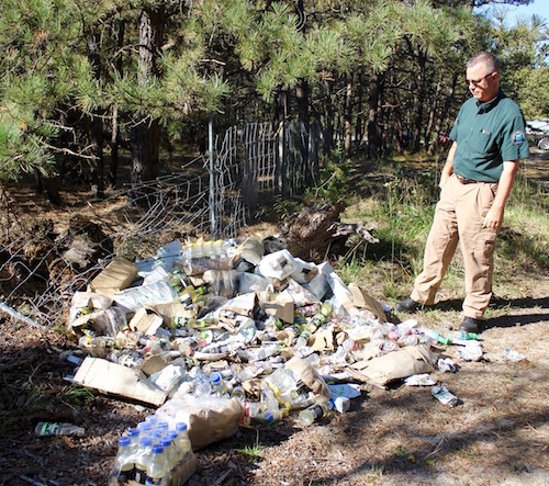 Central Pine Barrens Commission Compliance and Enforcement Officer Mike Lewis with one of the piles of energy drinks in the woods off Speonk-Riverhead Road.