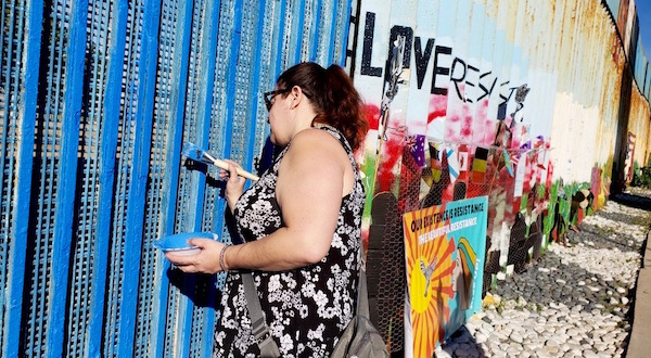 Lisa Votino-Tarrant paints a section of the border wall in Tijuana.