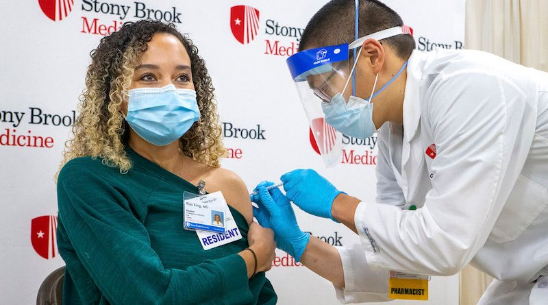 Kisa King, Resident in the Department of Emergency Medicine at Stony Brook University Hospital receives the first dose of the Pfizer vaccine, administered by Ian Pak, Pharmacist at Stony Brook University Hospital.