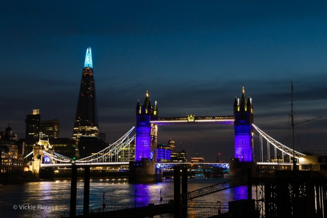 Tower Bridge and the London shard seen from Wapping are illuminated in blue