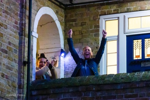 Wapping resident Kimi (R) cheers on the Greenbank Estate on a Thursday evening