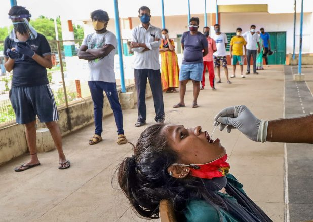 People standing in queue to give swab samples for Covid-19 tests in Bengaluru. (PTI Photo)
