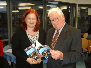 Co-author Emma GOlby-Kirk looks on, as Cllr Godfrey Olson inspects the new book