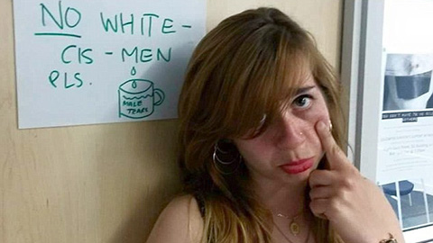 """Bahar Mustafa in front of a sign saying """"no white - cis - men"""". Pic: Change.org"""