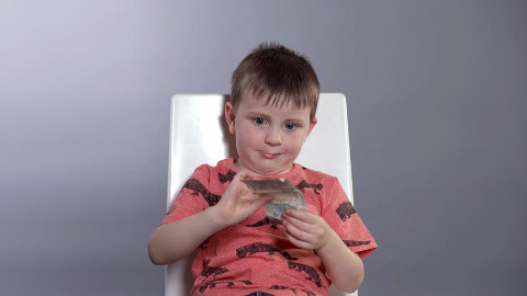 Children are made to choose between keeping a £5 note or donating it to charity. Pic: Brett Gascoigne
