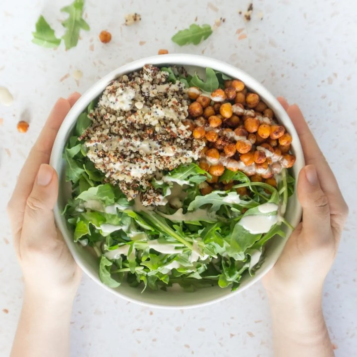 hands holding the chickpea bowls