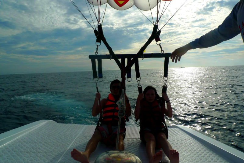 Evan and Raevian landing on boat after parasailing
