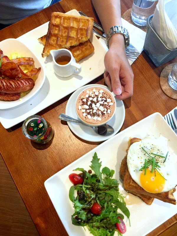 Monniker Brunch Spread with Hand holding Hot Chocolate