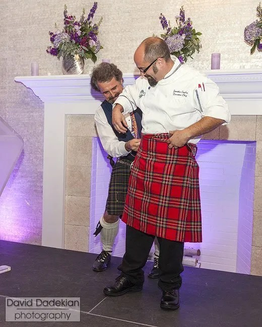 MC and auctioneer Sir Jeremy Bell presenting the 2012 Signature Chef Jonathan Cambra with his honorary kilt