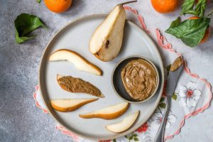 Pear Slices With Peanut Butter on White Plate