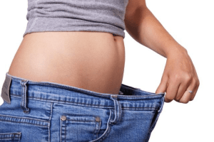 Girl holding blue jeans far from her flat exposed stomach.
