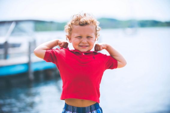 Curly haired boy in red polo standing in front of water.
