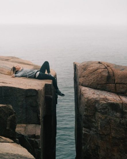 Woman lying on top of cliff.