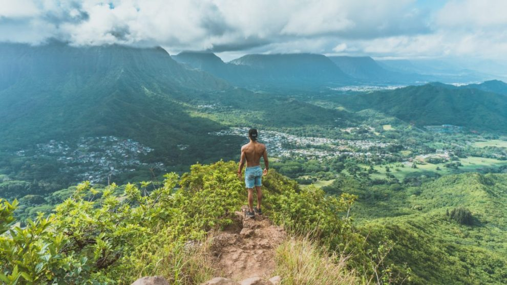 Guy On Top of Mountain With Shirt Off