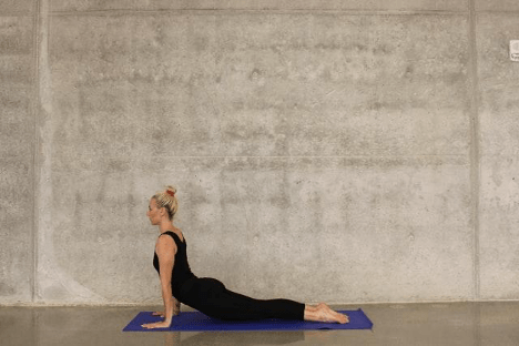 Woman Doing Yoga In Front of Blank Wall