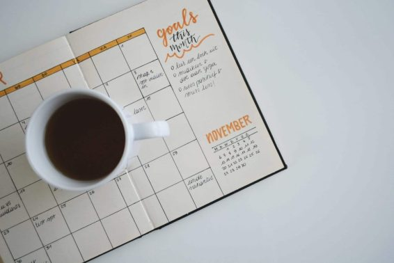 White Ceramic Mug of Coffee on Top of Day Planner