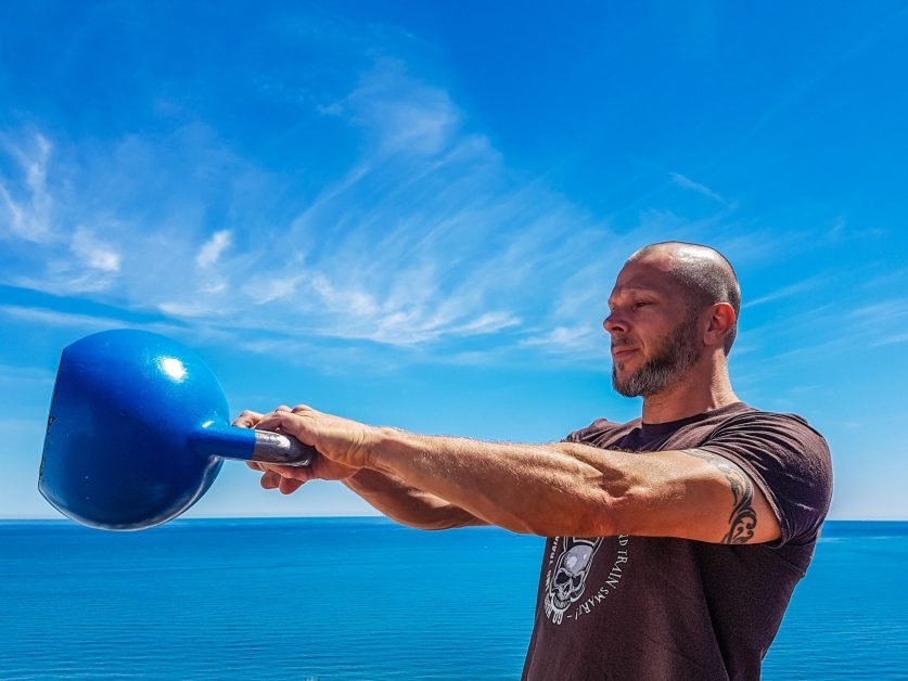 Man Swinging Blue Kettlebell