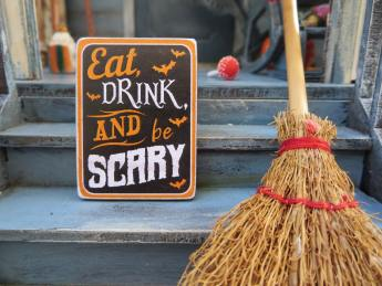 Eat Drink and Be Scary Sign Next to Pumpkin