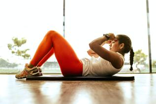 Woman Laying on Floor Doing Ab Crunch