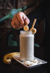 Person Putting Sliced Banana in Smoothie Glass Jar