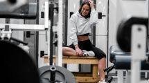 Woman Waring White Sweatshirt Smiling Sitting on Bench in Gym