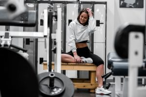 Woman Waring White Sweatshirt Smiling Sitting on Bench in Gym