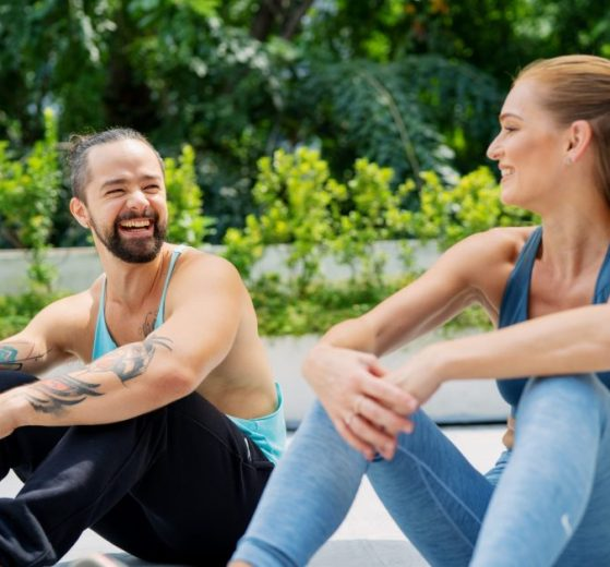 Man and Woman In Workout Clothes Sitting Next To Each Other Smiling
