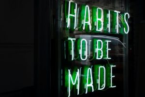 Green Neon Sign Saying Habits to be Made