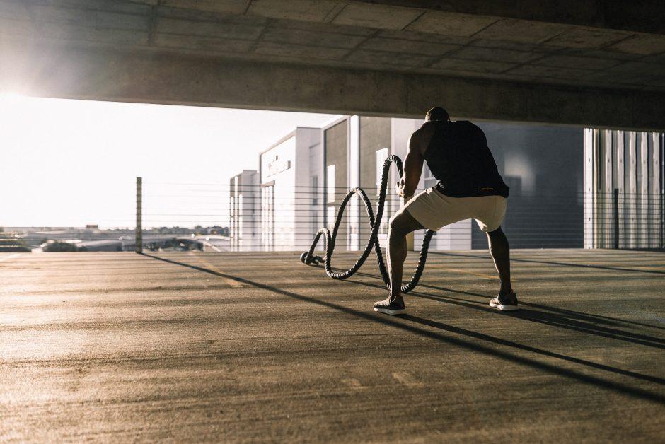 Man Using Battle Ropes in Garage