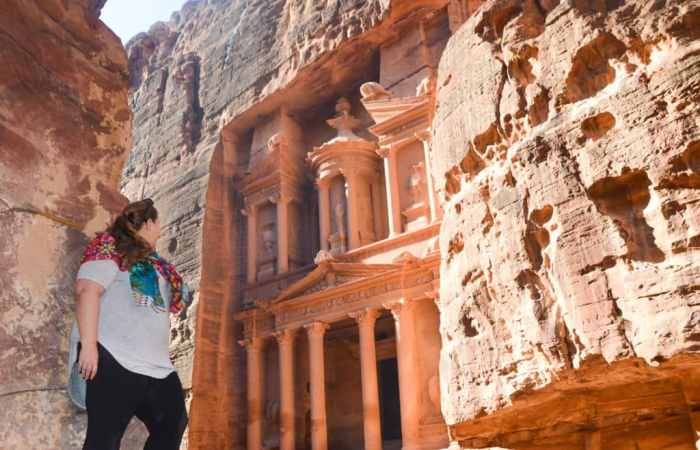 Standing on a rock looking to the Treasury of Petra in Jordan