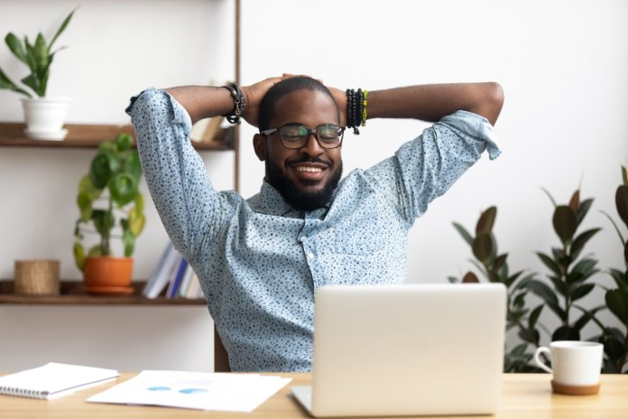 Afro-American businessman holding hands behind head sitting at office desk behind laptop