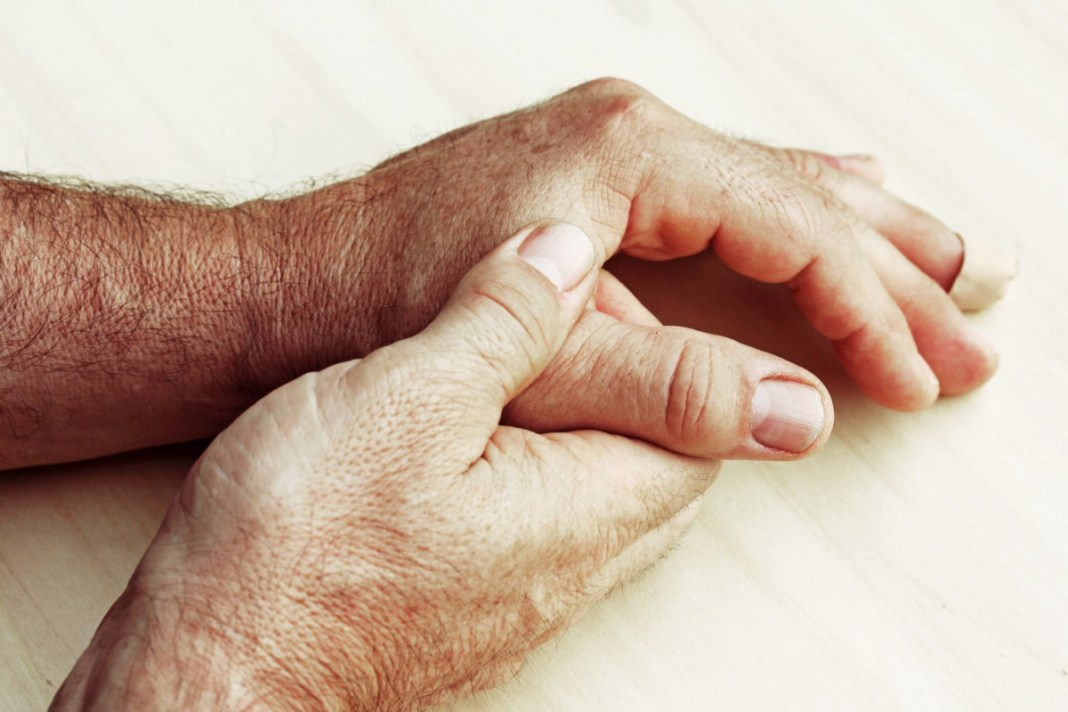 An elderly man has pain in his fingers and hands
