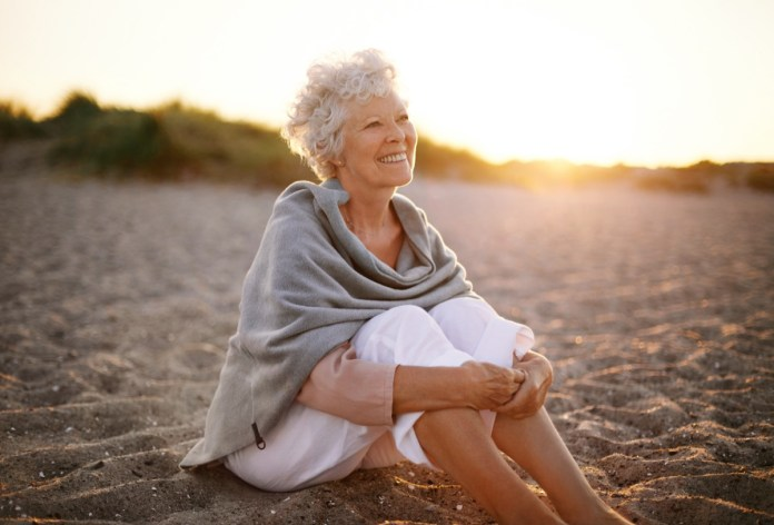 Senior caucasian woman sitting on the beach outdoors