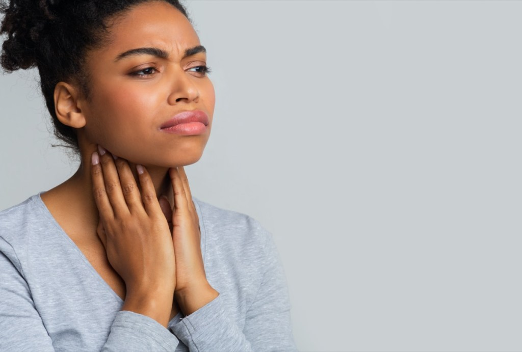 woman suffering from pain in throat, touching her neck, empty space.