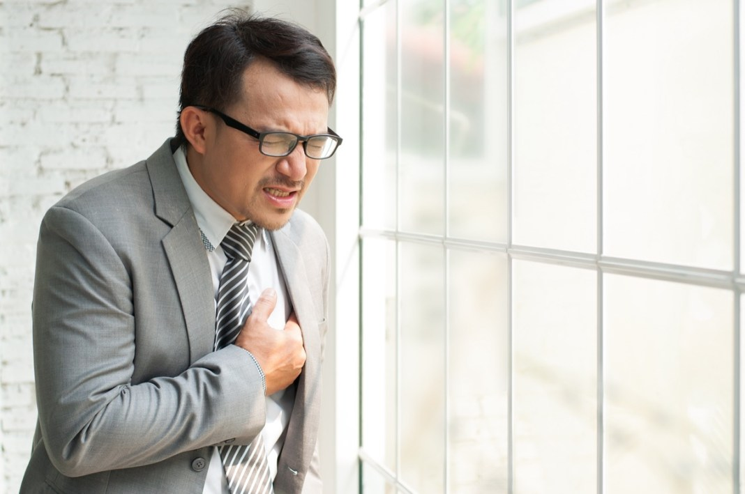 Asian Businessman standing near the window and having chest pain.