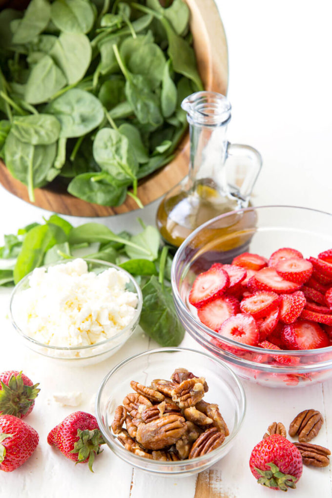 All the ingredients (not combined) of Strawberry Pecan Spinach Salad.