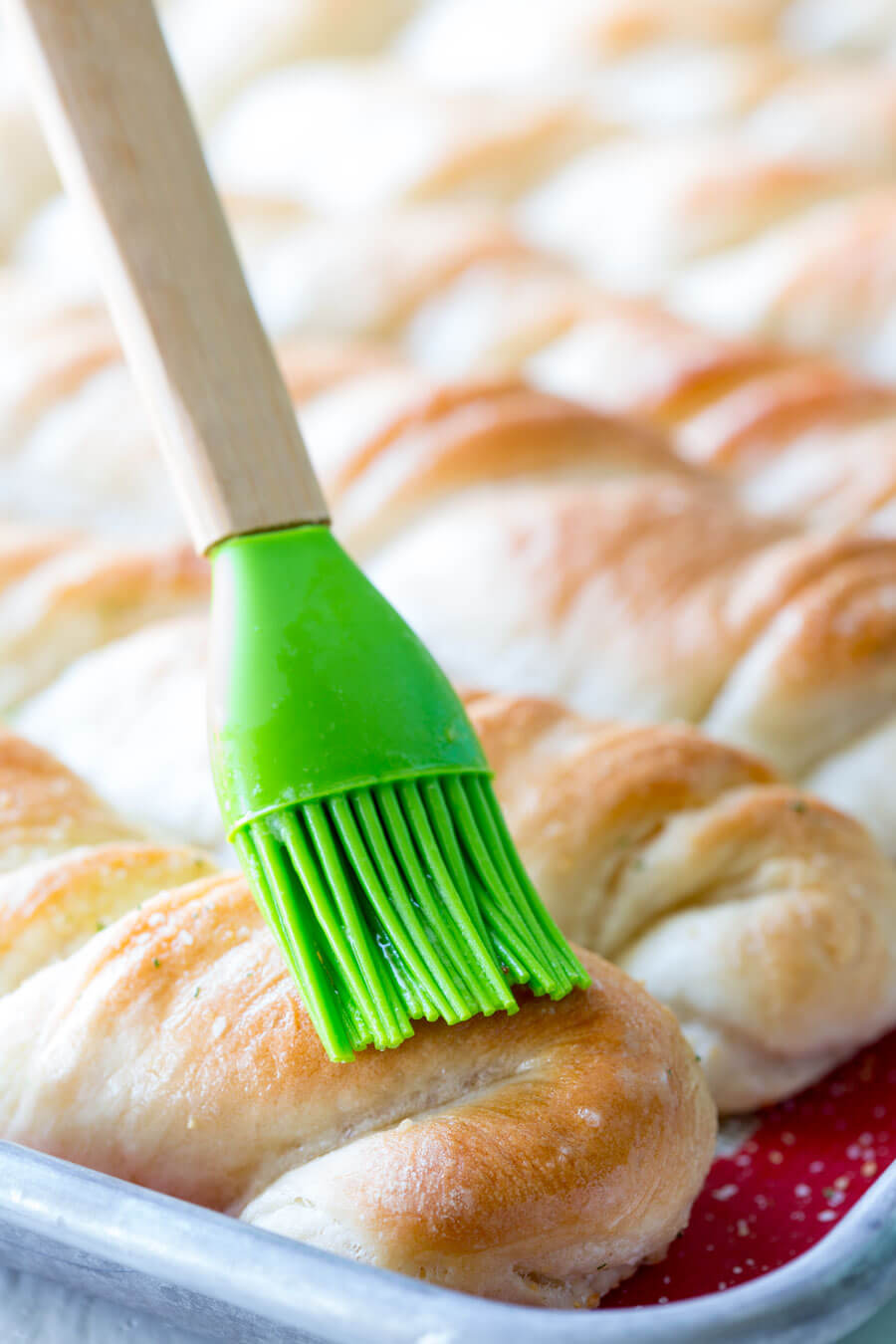 pastry brush spreading garlic butter on top of freshly baked garlic bread twists