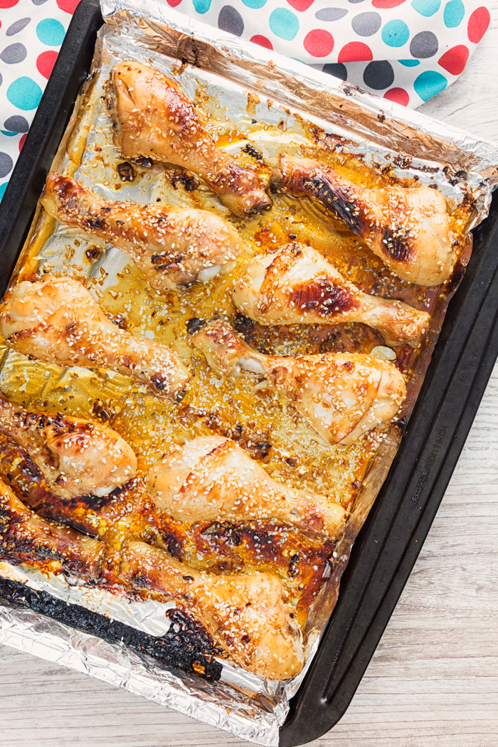 A cooking sheet with baked chicken drumsticks