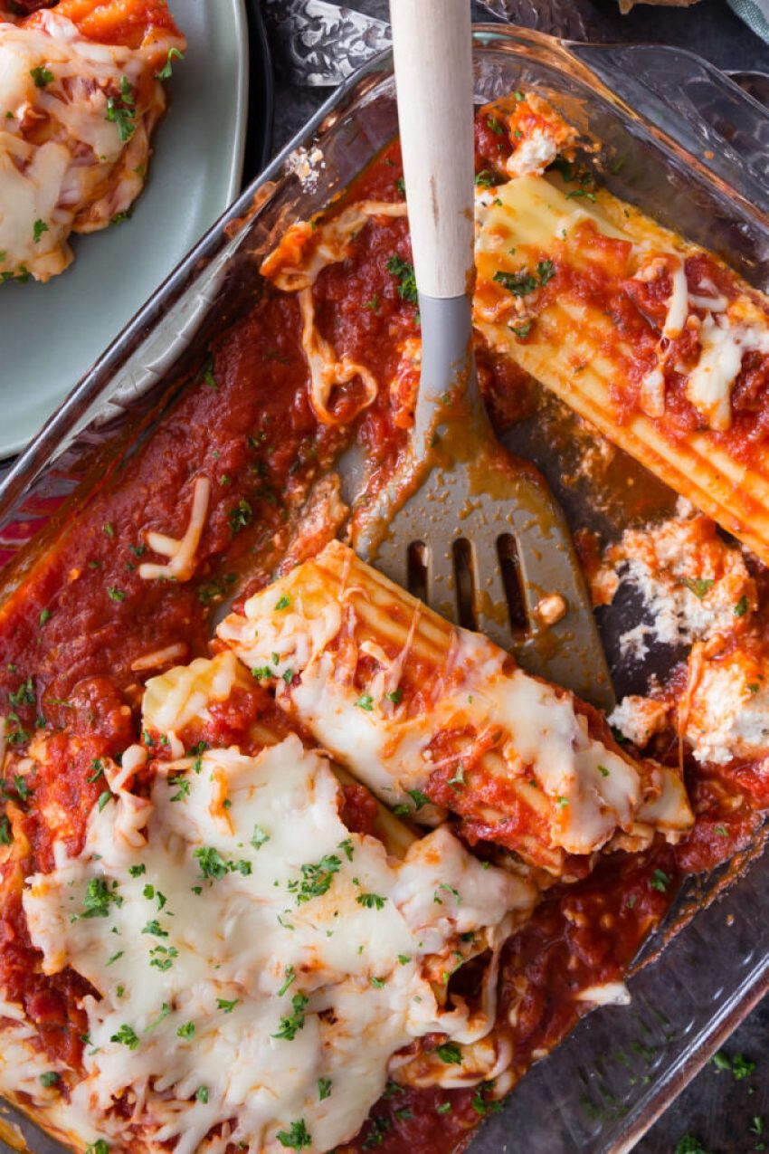 Cheese topped stuffed manicotti in a glass baking dish with a spatula