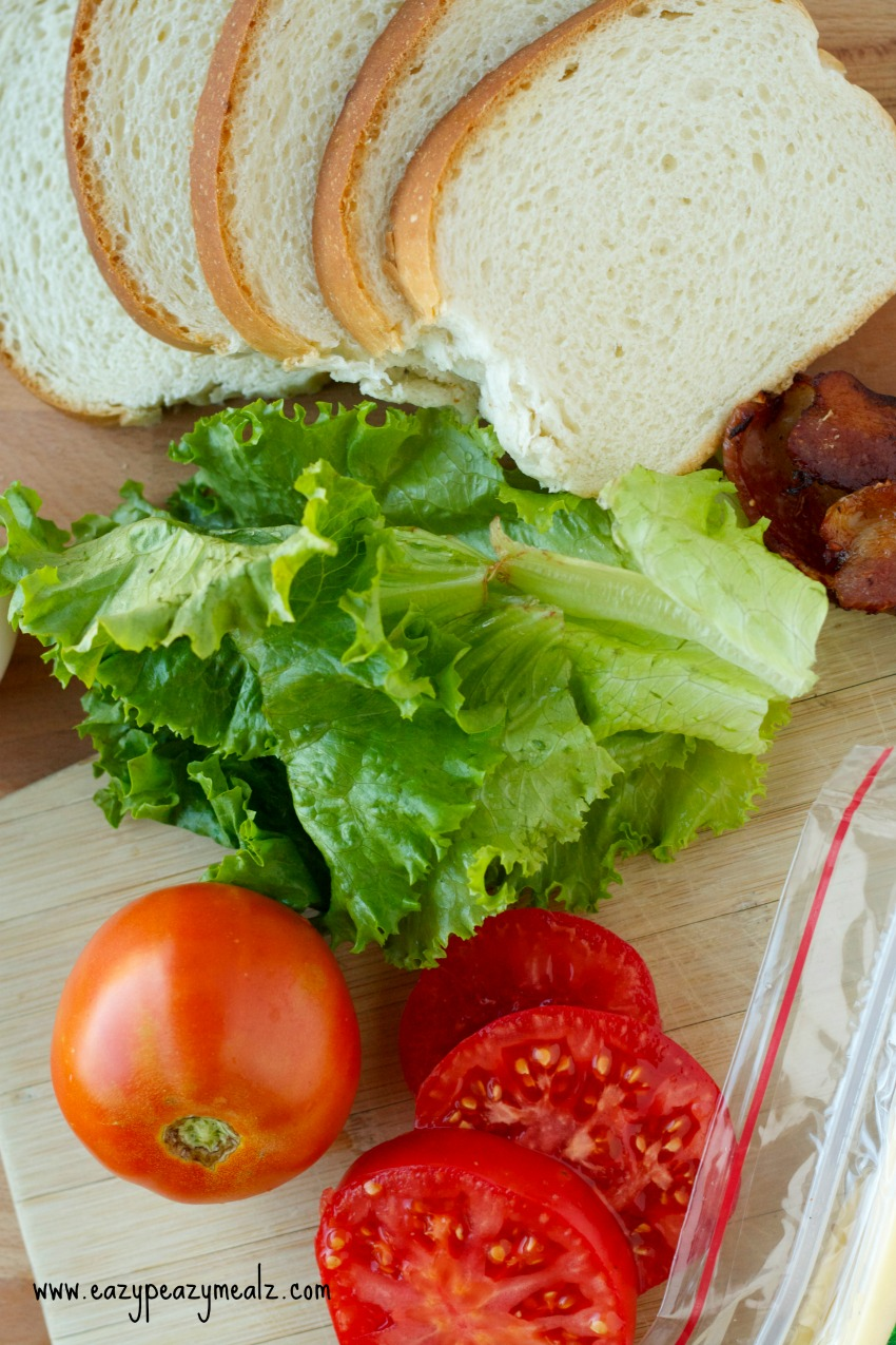 sandwich elements such as bread, lettuce, tomatoes and bacon under a wooden platter