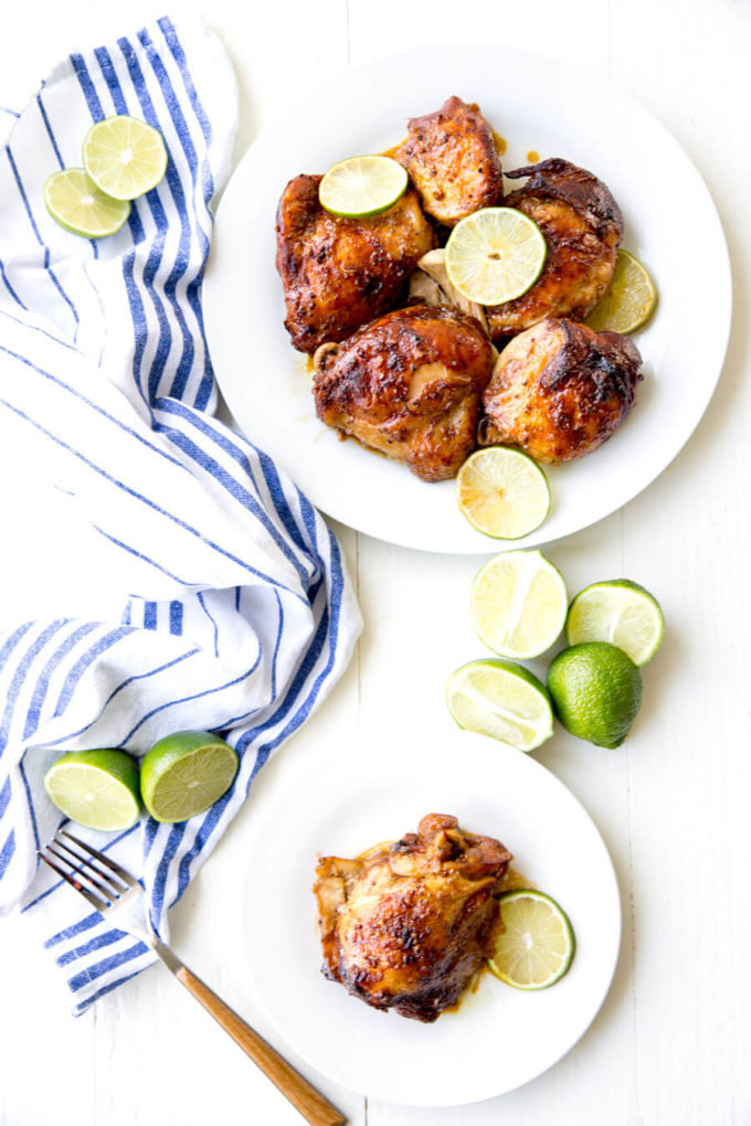Crockpot Garlic Lime Chicken on white plate, garnished with fresh lime slices.