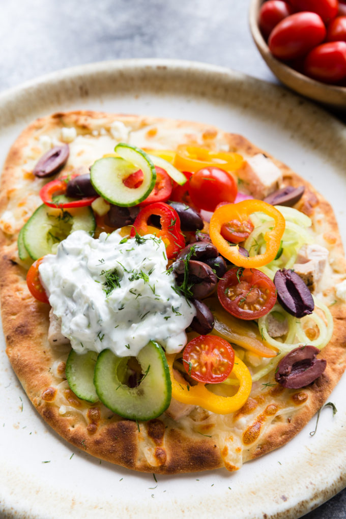 greek chicken flatbread on a cream colored plate. Topped with peppers, kalamata olives, cucumbers, tomatoes and cheese. With a sauce.