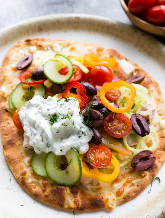 greek chicken flatbread on a cream colored plate. Topped with peppers, cucumbers, and other veggies.